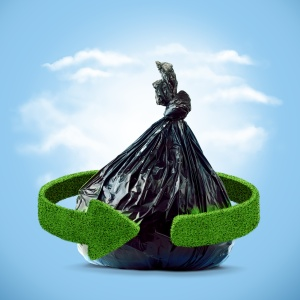 Garbage bag and green arrows from grass. Recycling concept