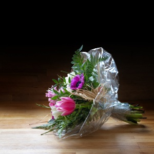 Bouquet of  spring flowers in cellophane on wood, dark backgroun