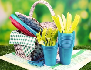 Bright plastic tableware on grass close-up