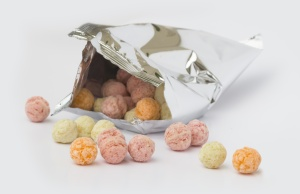 An opened aluminium bag of colorful sweet fruity flavor cereal balls on white background.
